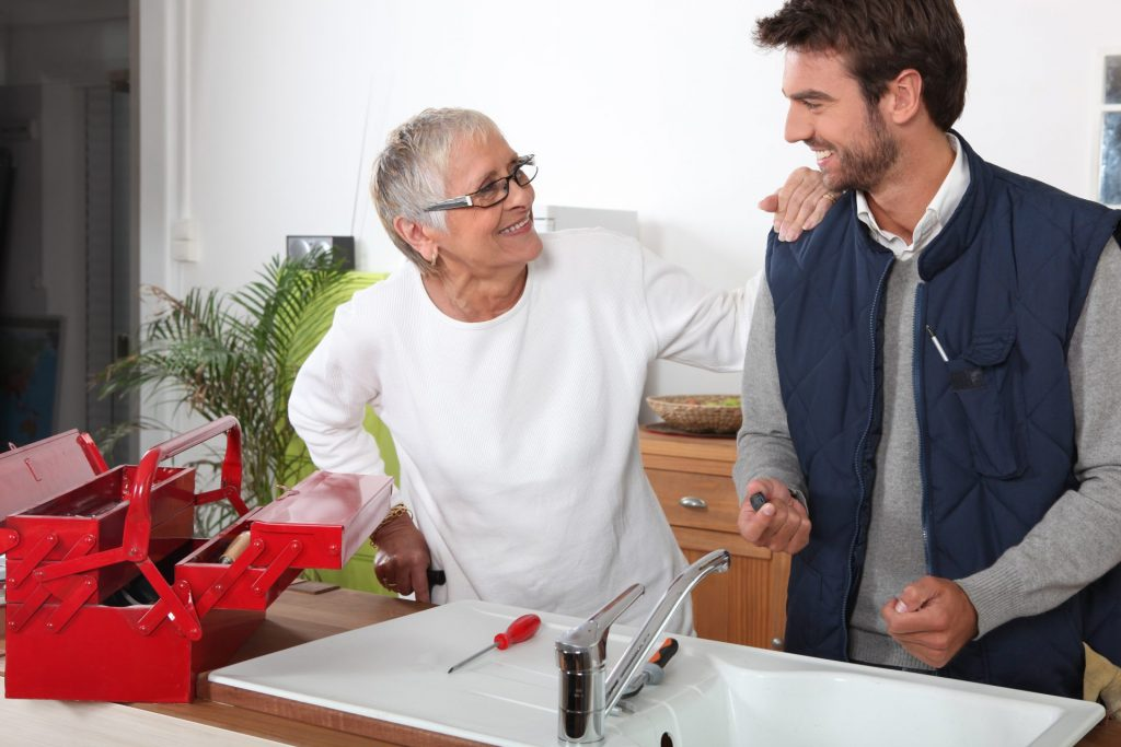 male carer providing respite care service to an elderly woman, with a toolbox next to the sink