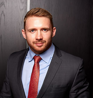 Photo of a bearded man in black suit, blue shirt and red tie smiling at the camera