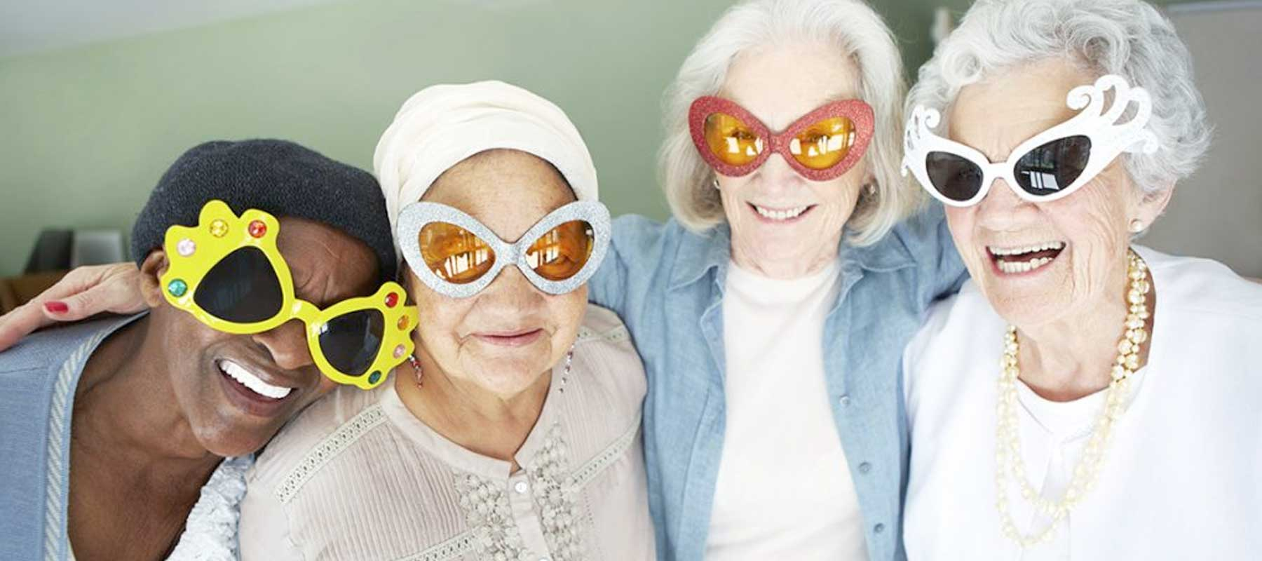 Four elderly woman in fun oversized glasses smiling in a nursing home
