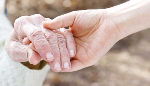 A younger person holds the hand of an elderly person