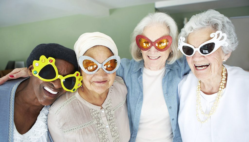 Four elderly woman in fun oversized glasses smiling at an aged care facility