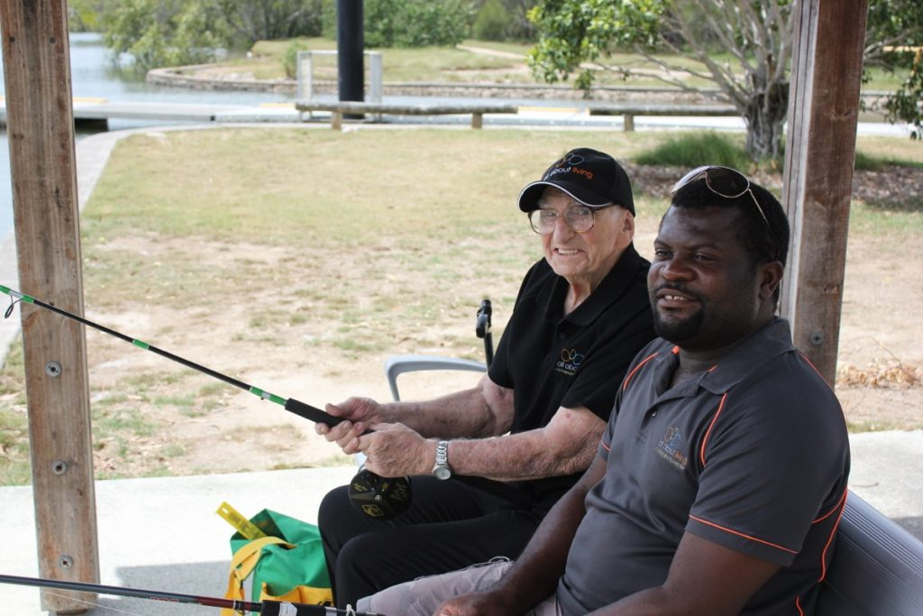 An elderly man and a carer sitting next to each other fishing and smiling, both men are wearing All About Living shirts