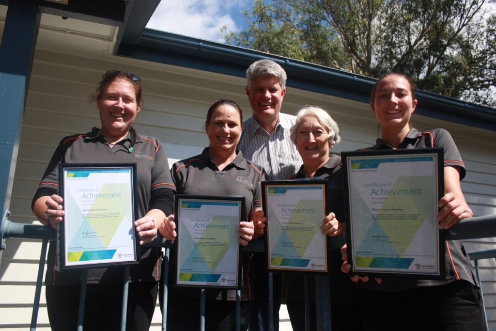 Four All About Living carers, nurses or volunteers smiling and holding certificate of achievement awards, a man in a grid suit stands behind them smiling