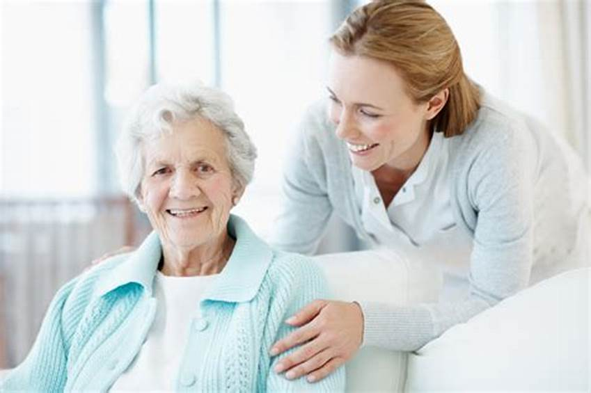 A female carer holds the shoulders of a happy elderly woman
