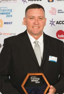 Photo of a man in a black suit and green tie holding a 'training awards 2019' award.
