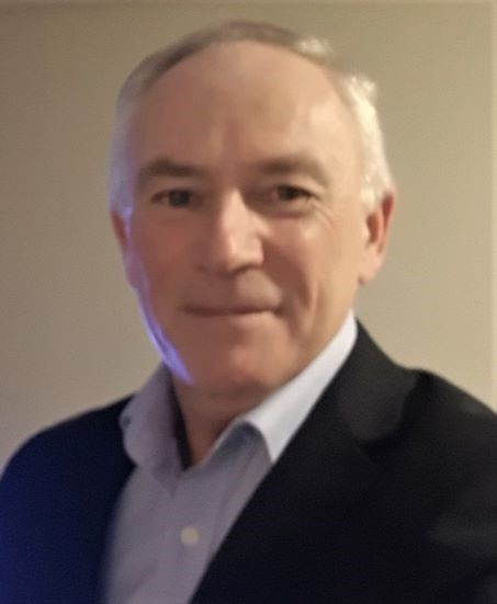 Photo of an elderly man in a black suit and blue shirt