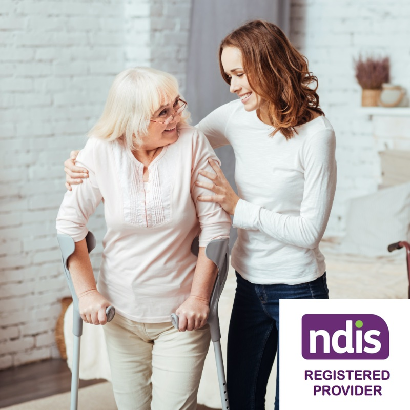 female carer holding the shoulders of elderly woman walking on crutches, ndis registered provider badge in the bottom right corner