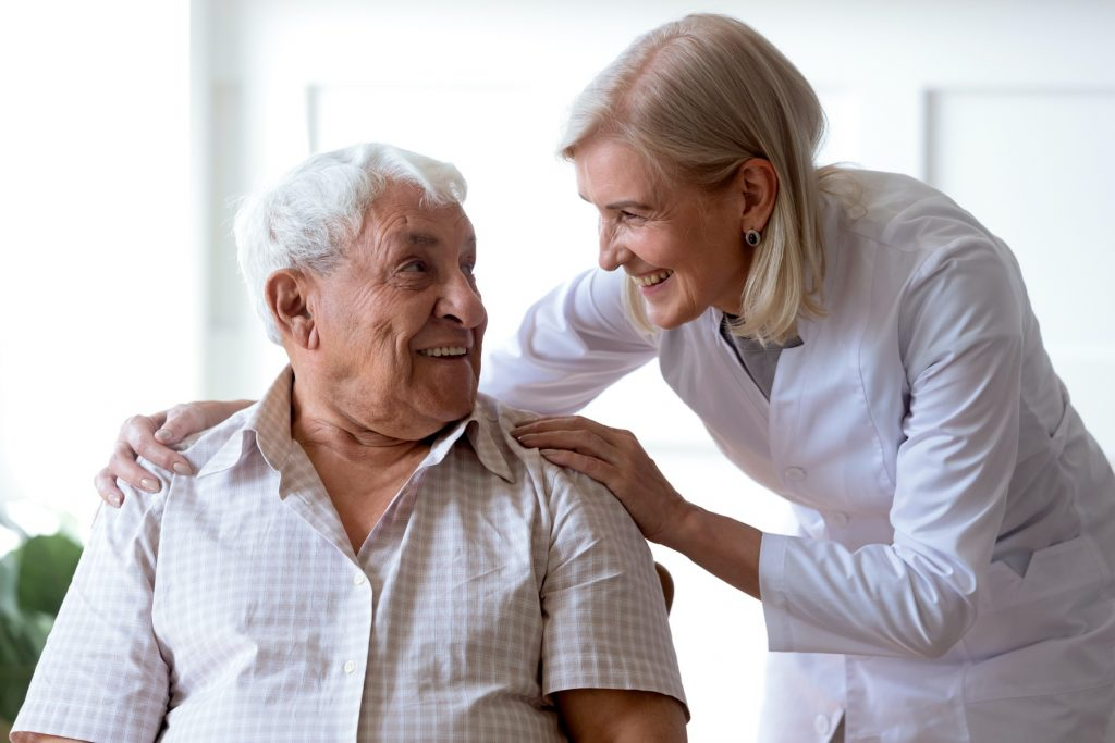 female nurse in white coat holding the shoulders of elderly man and smiling