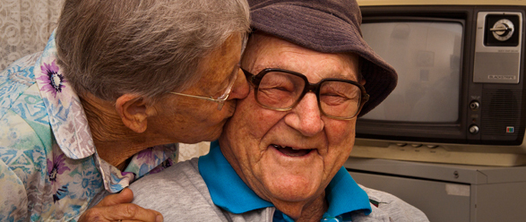 elderly woman kissing the cheek of an elderly man who is smiling