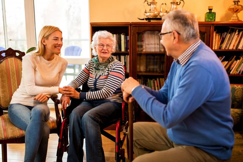 Sitting down, a woman holds the hand of an elderly woman in a wheel chair, who are both smiling towards an elderly man who is holding a walking stick and wearing a blue shirt