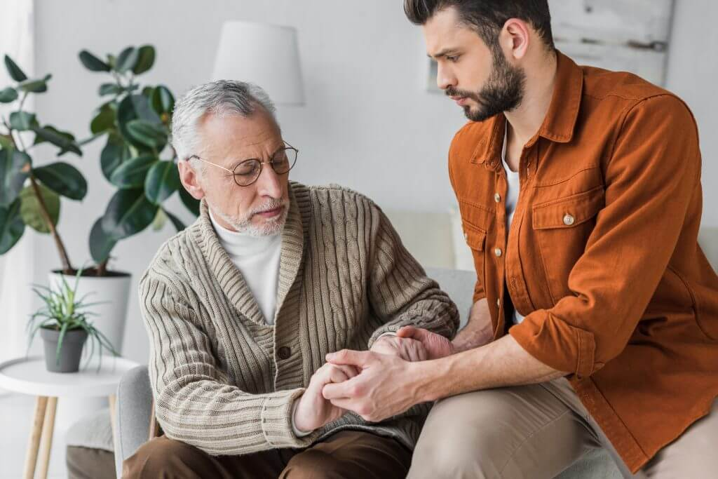 male carer nurse in orange shirt holding the hands of elderly man wearing a cardigan