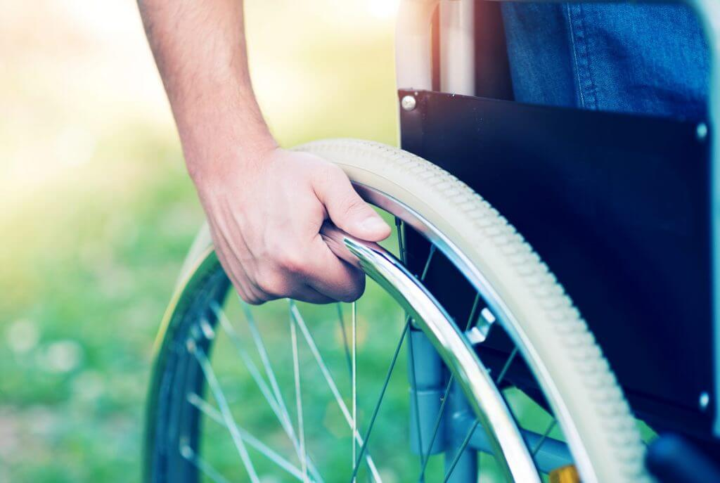 disabled man's hand on wheelchair wheel