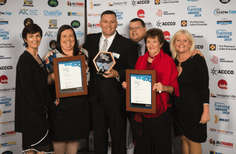 Six All About Living members formally dressed, taking a photo holding three Training Awards 2019 awards. Standing in front of a wall of brands including The Pharmacy Guild of Australia, Jobs Queensland, Tafe, MEGT, ACCCO