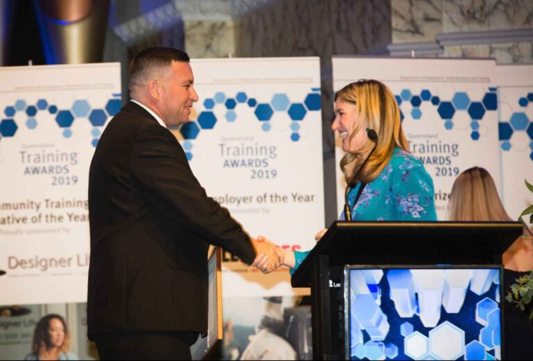 A man in a black suit shaking the hand of a smiling woman behind the podium, at the Training Awards 2019